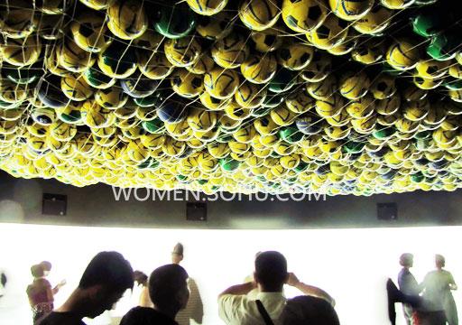 了一张巨大的网兜,并在其中塞进了数百个绿色,白色,蓝色,黄色的足球