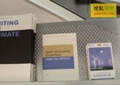 直击坎昆气候大会:搜狐绿色编辑制作的《坎昆气候大会媒体攻略手册》在展架上摆放供参会者阅读
