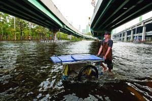 11月6日,在距离曼谷市中心不远处,一名商贩推车涉水前行。新华社/法新