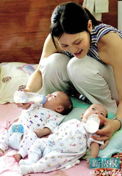 2003年5月15日下午,广州市郊的一座居民楼里,30岁的邓若静正为出生三个月的双胞胎儿子喂奶。陈海平/摄