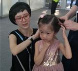 金巧巧为女儿蹲地扎小辫